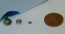 Figure 2: The scale required for future truly wearable EEG systems: a standard recording electrode, a large coin cell battery, unpackaged electronics and a British one pence piece for scale. Ideally the recording electrode would be the single largest component present. Photo: Eduardo Aguilar-Pelaez.