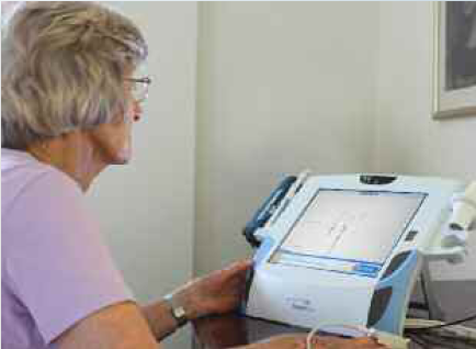 Figure 1: A patient uses TeleMedCare's telehealth system to record a single lead electrocardiogram.